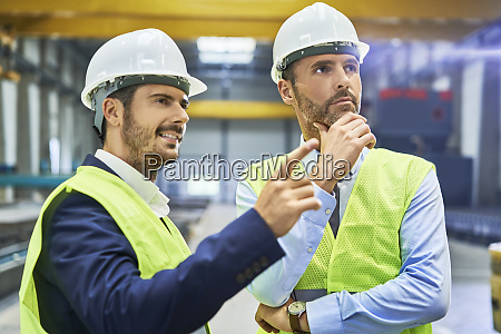 two managers wearing protective workwear talking