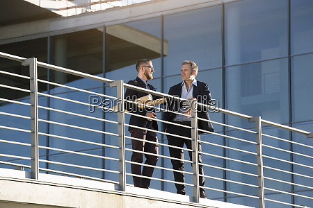 two businessmen talking on a bridge