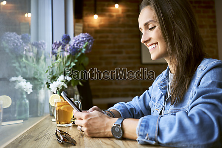 smiling young woman using phone in
