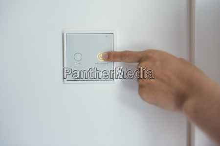 woman using smart home switch on