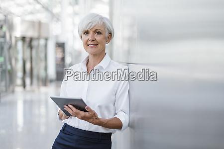 portrait of smiling senior businesswoman holding