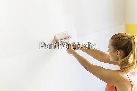young woman painting wall at new