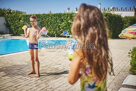 girl with water gun splashing at