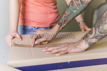 die hand oeffnet die kartonbox mit