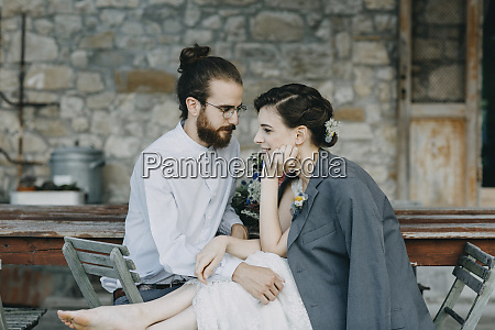 affectionate happy bride and groom sitting