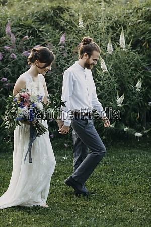 bride and groom walking hand in