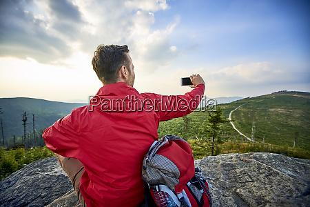 man sitting on rock taking picture