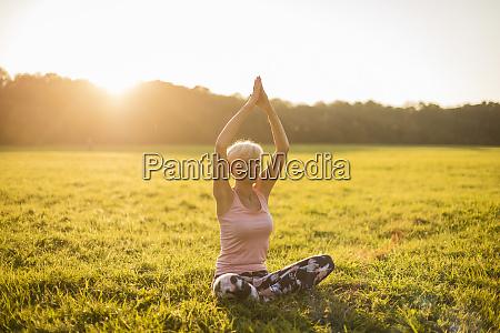 senior woman doing yoga on rural