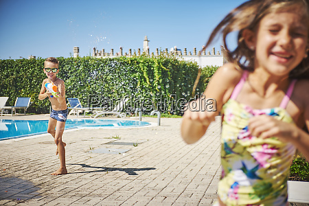 boy with water gun splashing at