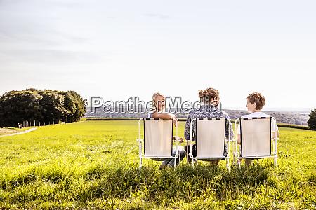 freunde sitzen auf campingstuehlen in laendlicher