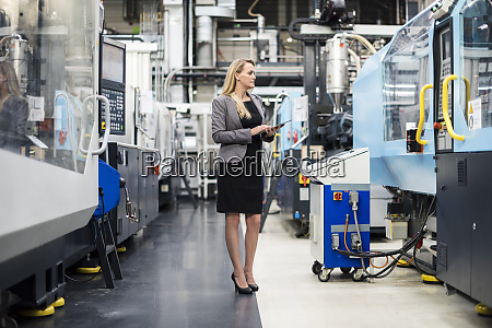 woman using tablet at machine in