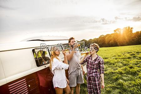 friends in pyjamas drinking beer at