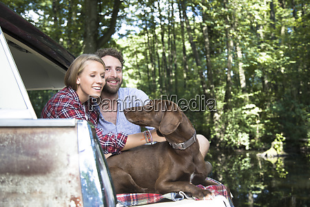 smiling young couple with dog sitting