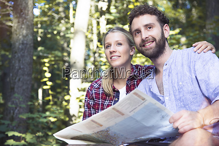smiling young couple with map in