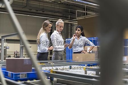 three women discussing at conveyor belt
