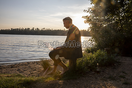 mature businessman sitting at lakeshore by