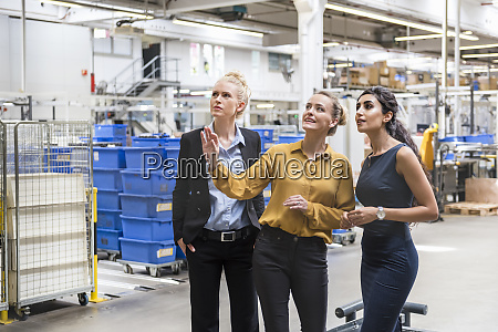 three women talking in modern factory