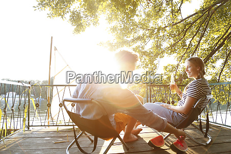 young couple sitting on a jetty