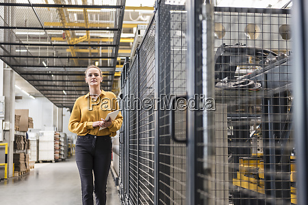 woman with tablet walking in factory