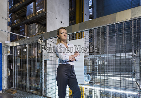 blond woman in high rack warehouse