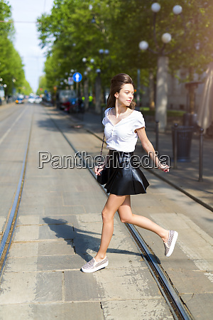 young woman crossing a street with