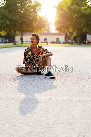 smiling young woman sitting outdoors at