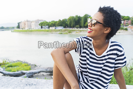 smiling young woman wearing sunglasses sitting