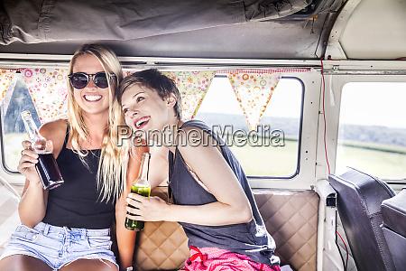 two happy women inside van with