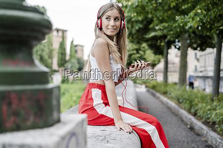 smiling teenage girl wearing headphones listening