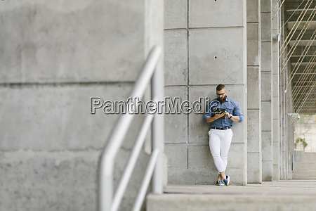 bearded hipster businessman leaning against concrete