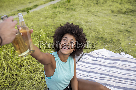 happy woman sitting outdoors clinking beer