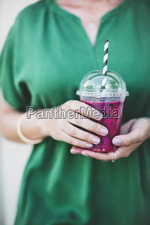 womans hands holding plastic cup of