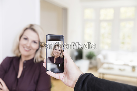 man taking photo of woman with