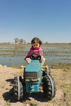 baby maedchen faehrt einen spielzeug traktor
