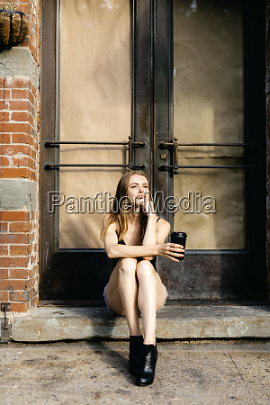 young woman sitting in the street