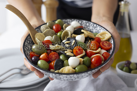 woman showing mediterranean orecchiette with tomato