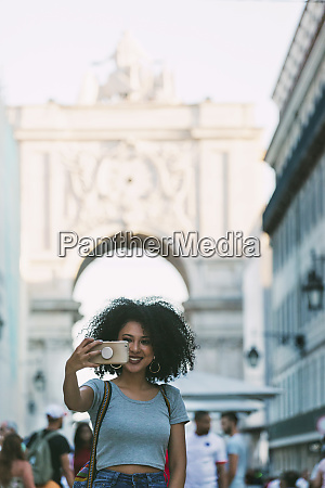 young woman with smart phone taking