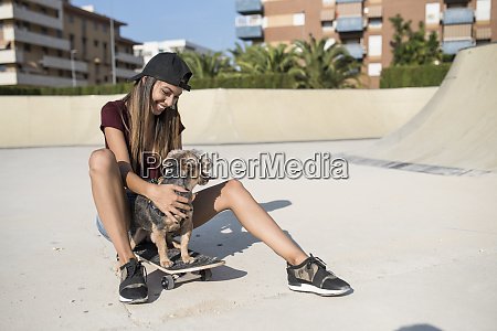 young woman sitting on skateboard stroking