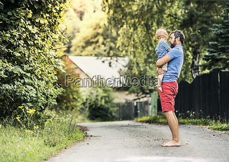 barefoot father carrying barefoot little son