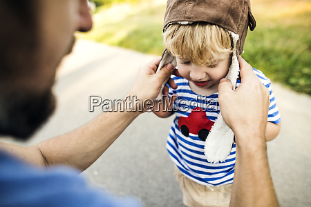 father putting on pilot hat for