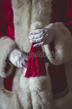 hand des weihnachtsmanns haelt weihnachtskappe