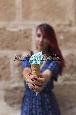 young woman holding blue icecream into