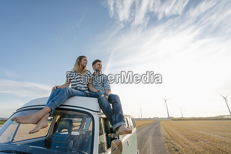 couple sitting on camper van in