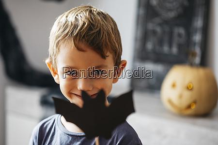 portraet laechelnder kleiner junge mit pappkarton