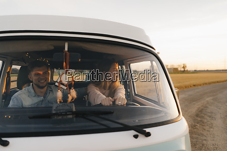couple driving camper van on dirt