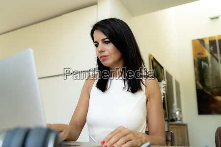 dark haired woman using laptop at