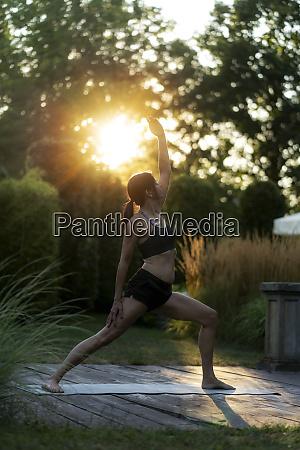 woman practicing yoga in garden