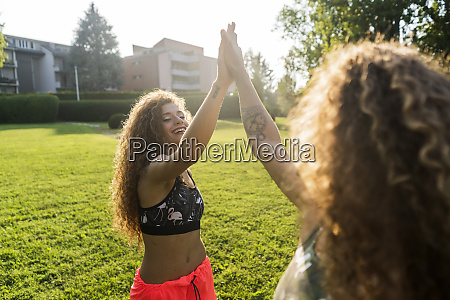 laughing young woman high fiving with