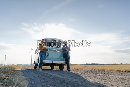 happy couple standing at camper van
