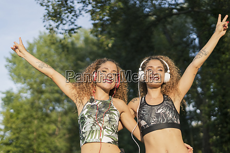 portrait of smiling twin sisters listening